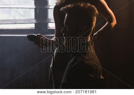 Private barbershop in dark place. Male style. Mystery atmospheric workplace, unrecognizable female hairdresser with electric razor. Stylish haircut, man in focus on foreground, beauty concept