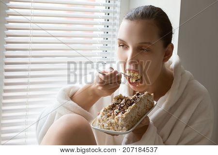 hungry fun pretty girl with sweet cake on window eating