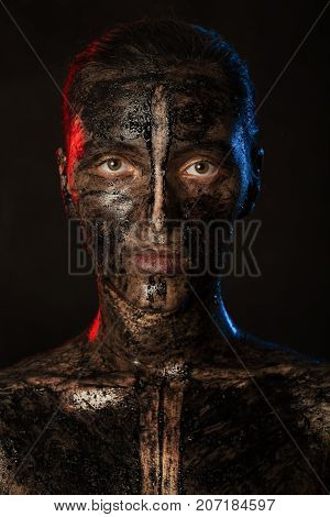 woman with black dirty smeared make up on black background