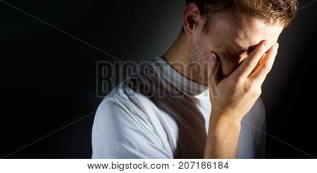 man with a hand on his face on a dark background facespalm