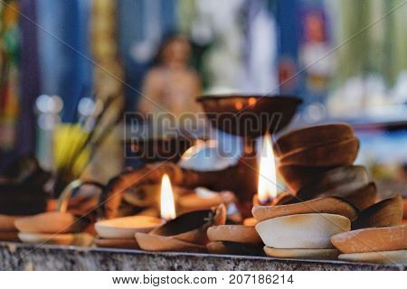 Burning old textured candles with defocussed background of the most popular Hindu shrines outside India - Batu Caves. Mood of sacrament and revelation.