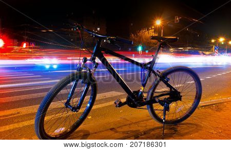 a bicycle on the street in a night against a background of blurry lights from cars the light trails on the street
