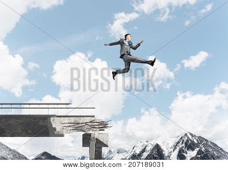 Businessman jumping over huge gap in concrete bridge as symbol of overcoming challenges. Skyscape and nature view on background.