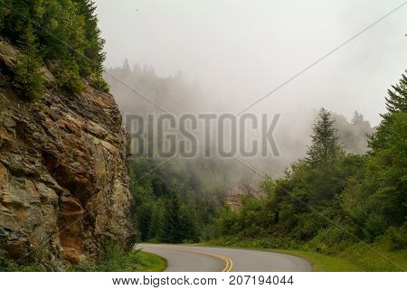 Smokey Mountain Parkway surrounded by cliff, forest, and clouds.