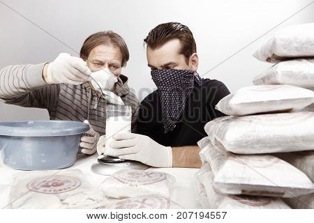 Two dealers packing lot of drugs for distribution poster