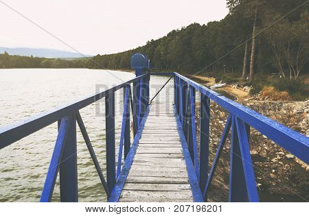 Mole  on the scandinavian lake with motorboat on side and misty hills. Blue wooden bridge in forest in autumn time with blue lake. Lake for fishing with pier and powerboat. Foggy lake with hills