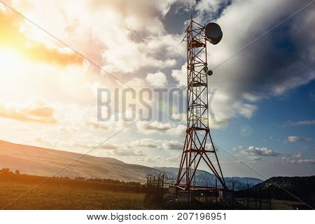 Telecommunication tower with dish and mobile antenna on mountains at sunset sky background, toned