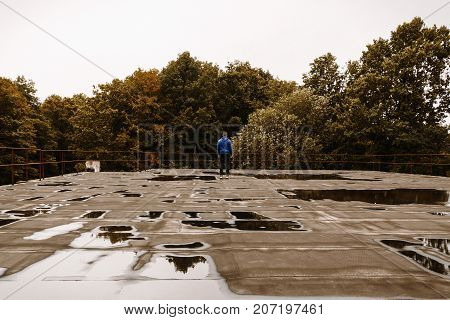 Young criminal guy standing on the roof top of old hotel in forest in autumn.  Man hooligan sneaked to the old hotel balcony with water. Faceless man in hood on rooftop with forest background