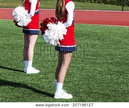 Two high school cheerleaders are standing at attention with their pompoms behind them getting ready to start their routine.