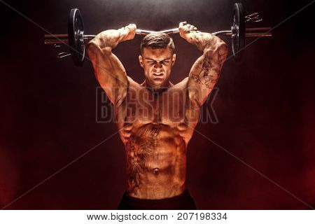 Portrait of muscular man lifting dumbbell in red smoke. Studio shot. Exercise for triceps. Motivation.
