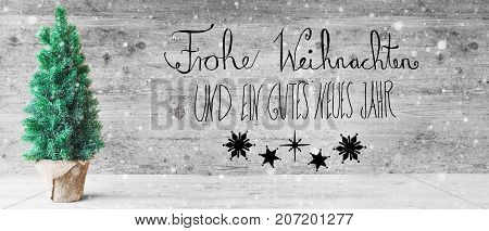 Calligraphy With German Text Frohe Weihnachten Und Ein Gutes Neues Jahr Means Merry Christmas And Happy New Year. Green Christmas Tree With Gray Wooden Background And Snowflakes.