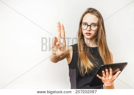 sullen beautiful girl with a tablet in her hands and a black dress shows two fingers