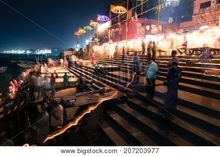 VARANASI INDIA - MARCH 13 2016: Long exposition picture at night of moving indian people at Dashashwamedh Ghat in Ganges River after religious Ganga Aarti ritual in Varanasi India.