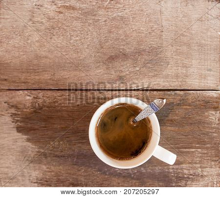 Cup of coffee on a wood table background. Top view with copy space