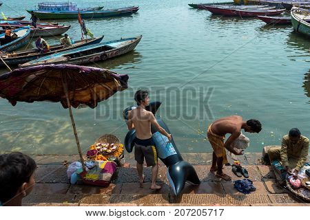 VARANASI INDIA - MARCH 14 2016: Horizontal picture of Japanese man holding a whale pool float at Dashashwamedh Ghat in Ganges River during day time in Varanasi India.