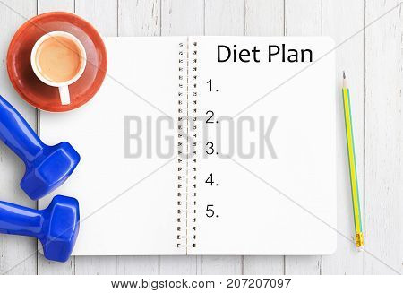 Top view of diet plan paperpencilcup of coffee and blue dumbbell on white wooden table background with copy for any design. Healthy eating dieting slimming and weight loss concept.