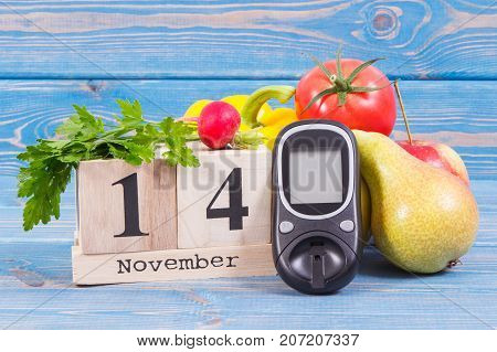 Date of 14 November on cube calendar glucometer and fresh fruits with vegetables concept of world diabetes day