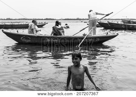 VARANASI INDIA - MARCH 14 2016: Horizontal black and white picture of indian child bathing at Dashashwamedh Ghat in Ganges River during day time in Varanasi India.
