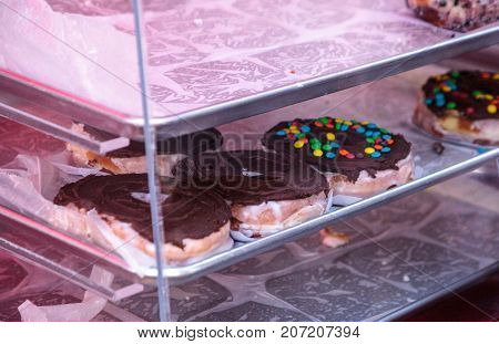 Doughnuts with chocolate fudge frusting baked fresh and in the window of a bakery