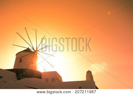 Wind mills at Oia town on Santorini island, Greece. Traditional and famous houses and churches with blue domes over the Caldera, Aegean sea