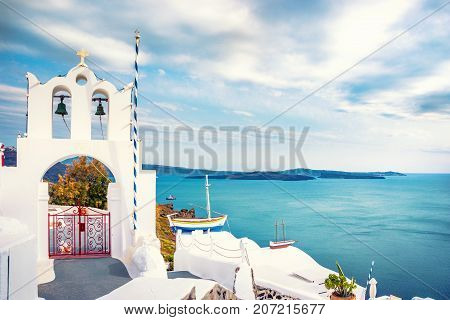 Bell tower of an orthodox church at Santorini Greece. Honeymoon summer aegean cycladic background.