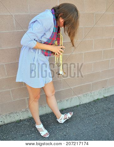 Female jazz trumpet player blowing her horn outdoors.