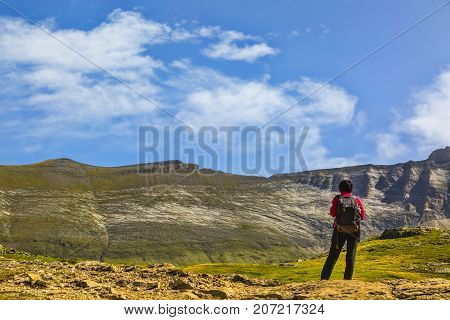 Female hiker admiring the landscape from the center of the glacial Circus of Troumouse one of the largest from the Europe.