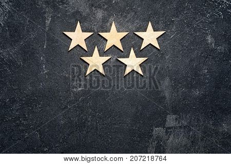 Five wooden stars arranged in two rows 3 on the top and 2 below on a dark cement background with copy of the space. Concept of service rating and quality of trade. Top view copy space for your text