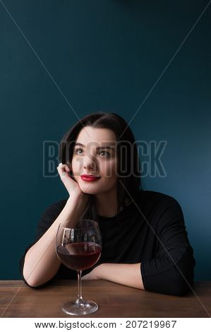 Alone dreaming young female in bar. Future perspectives in life, melancholic mood with red wine on blue background with free space, dream concept