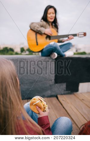 Music junkie with junk food on live show. Girl with fastfood in hands listen singer's acoustic guitar improvisation.