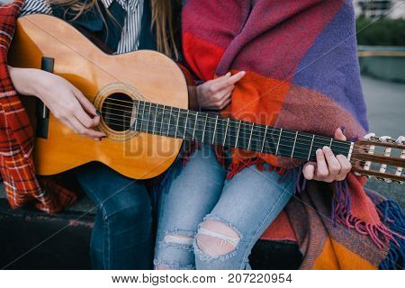 Playing guitar and meeting on roof, close up. Two girls studying music together, unusual places for rest and communication, sharing time in close and cheerful atmosphere concept