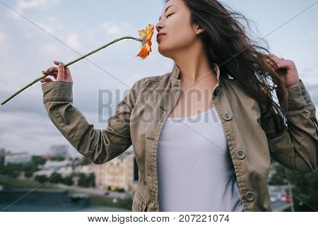 Close up beautiful girl sniffs scent of orange flower on urban city background. Airness and fly, freedom and romantic dreams, happiness and love concept