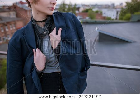 Enigmatic young woman wearing in man's jacket on urban city background. Close up of tenderness and romance, melancholy and love concept