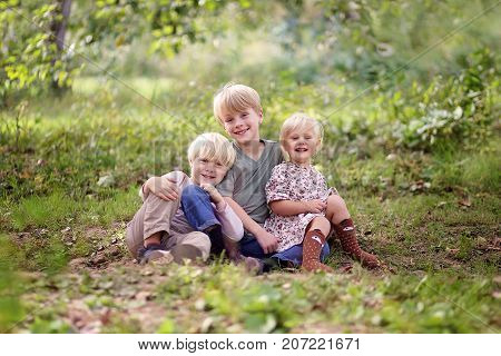 A portrait in the forest of three happy smiling young children an eight year old boy his baby sister and his 5 year old little brother.