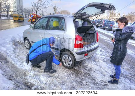 MINSK REPUBLIC OF BELARUS - January 16.2017: Man changes a leaky tire on my personal car