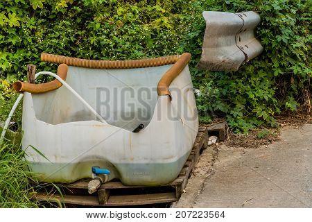 Large plastic container modified to catch water sitting on a wooden pallet in front of lush green bushes with part of guardrail in the bushes