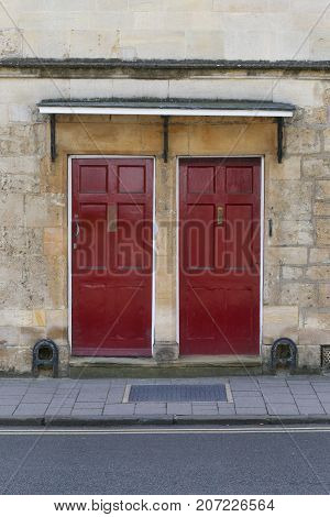 Two Dark Red Front Doors On The Stone Wall
