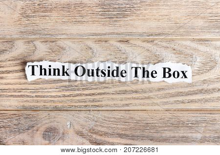 Think Outside The Box text on paper. Word Think Outside The Box on torn paper. Concept Image.
