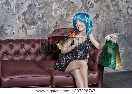 Girl With Bags Sitting On Sofa On Grunge Wall