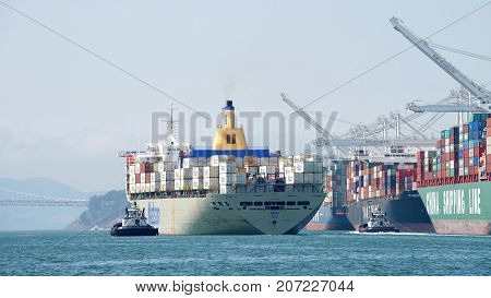Oakland CA - September 05 2017: Tugboats SANDRA HUGH and REVOLUTION assist Matson Cargo Ship MANOA to maneuver out of the Port of Oakland the fifth busiest port in the United States.