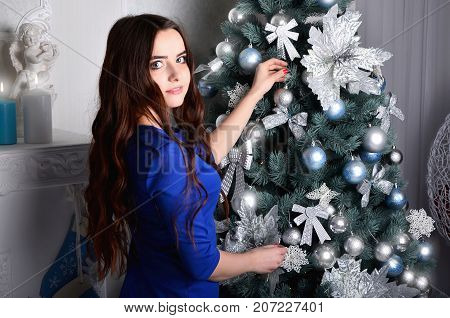Girl In A Blue Dress Decorates A Christmas Tree
