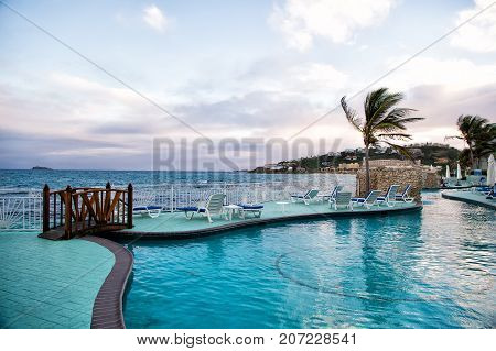 Swimming pool with blue water and panoramic sea view on cloudy sky background in Philipsburg Sint Maarten. Lounge and sunbeds on tropical beach. Summer vacation in paradise. Luxury lifestyle concept.