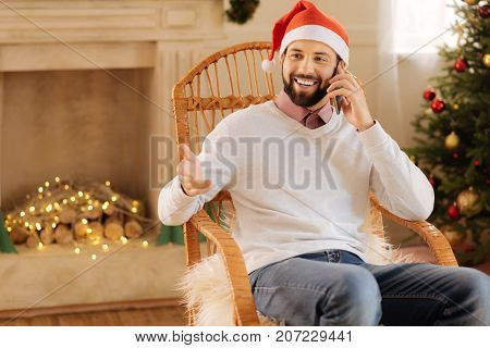 Lively conversation. Pleasant smiling man in a Santa hat talking on the phone while sitting in a cozy rocking chair in a room with Christmas decorations