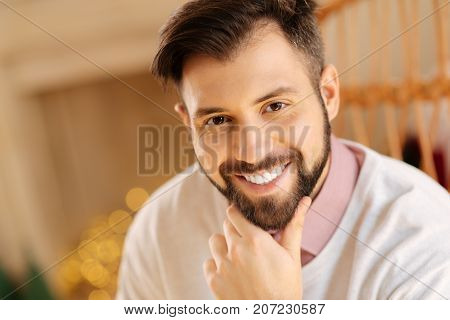 Masculine beauty. The portrait of a handsome cheerful young man sitting in a rocking chair and smiling at the camera while touching his chin with his fingers