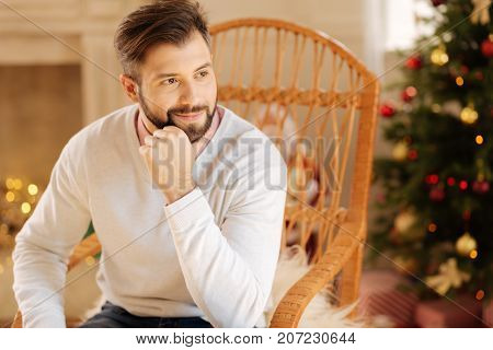 Calm day. Charming dark-haired man sitting in a rocking chair in a room decorated for Christmas and posing, resting his chin on his hand and looking away