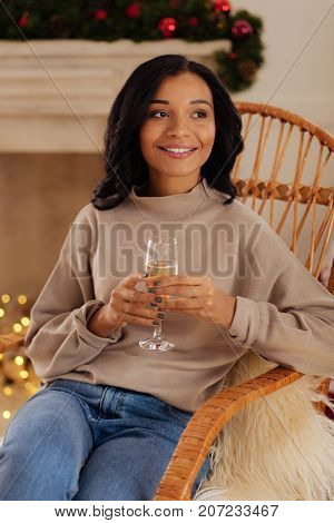 Pleasant coziness. Charming dark-haired young woman sitting in a rocking chair and holding a glass of champagne in her hands