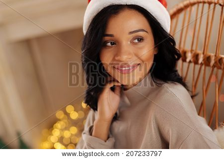 Refined beauty. Gorgeous dark-haired young woman with a swarthy complexion posing in a rocking chair and touching her neck while wearing a Santa hat
