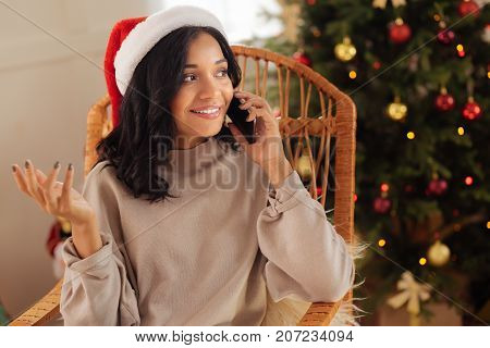 Pleasant discussion. Charming dark-haired woman in a Santa hat sitting in the rocking chair and talking on the phone while smiling happily