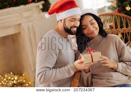 My personal Santa. Happy young woman sitting in a rocking chair and cuddling her husband giving her a Christmas present while both of them wearing Santa