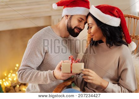 Only you. Tender young man giving his beloved wife a New Year present while pressing his forehead against hers, both of them wearing Santa hats poster